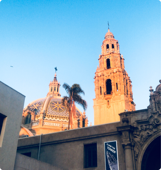 The tops of the Museum of Us and the California Tower in Balboa Park in front of a blue sky.