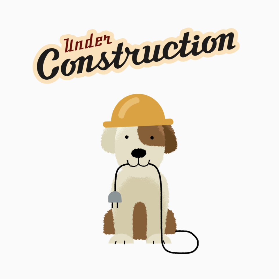 Dog wearing a construction hat holding an electric plug in its mouth underneath a sign that says Under Construction.